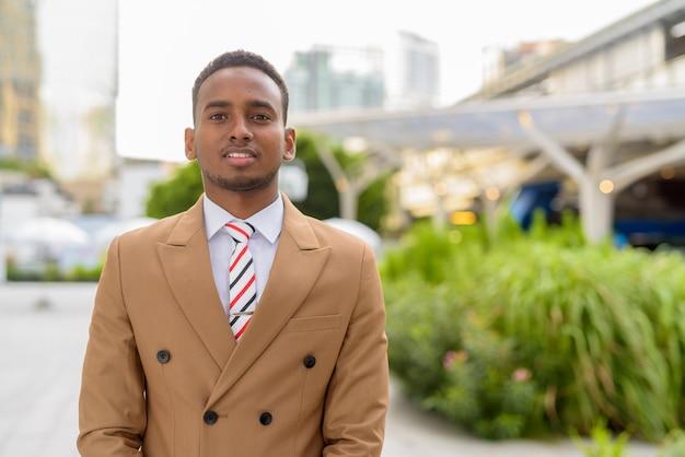 Glücklicher junger hübscher afrikanischer geschäftsmann, der in der stadt draußen lächelt Premium Fotos