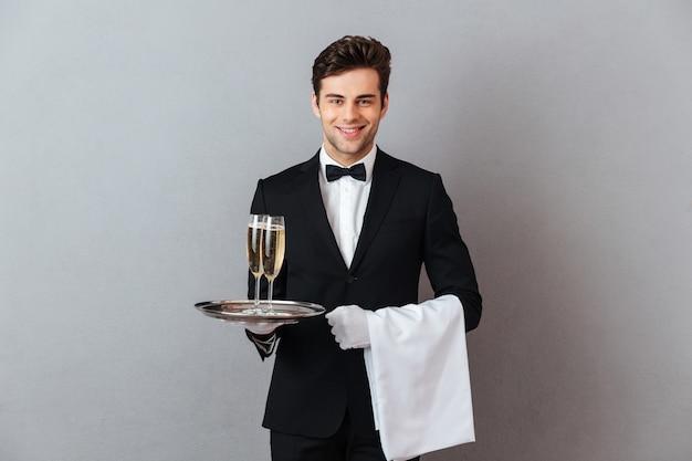Glücklicher junger kellner, der glas champagner und tuch hält. Kostenlose Fotos