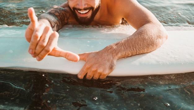 Glücklicher junger kerl mit der shaka geste, die auf brandungsbrett im wasser liegt Kostenlose Fotos