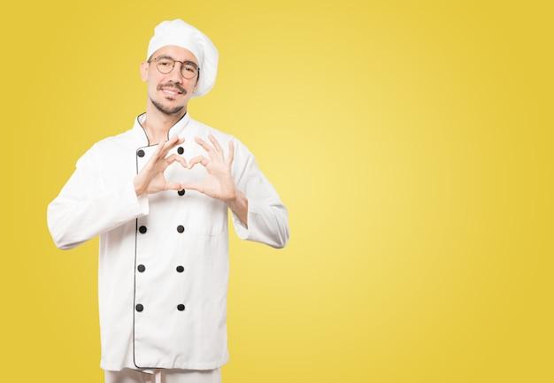 Glücklicher junger koch, der eine geste der liebe mit seinen händen tut Premium Fotos