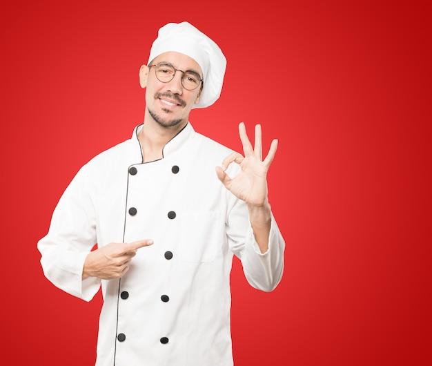 Glücklicher junger koch, der eine richtige geste tut Premium Fotos