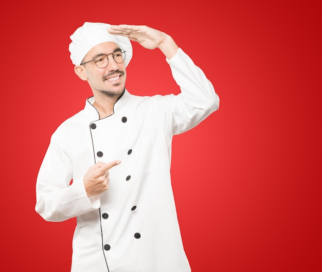 Glücklicher junger koch mit einer geste des wegschauens Premium Fotos