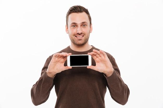 Glücklicher junger mann, der anzeige des handys zeigt Kostenlose Fotos