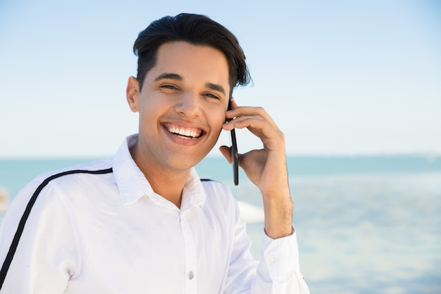 Glücklicher junger mann, der draußen um smartphone ersucht Kostenlose Fotos