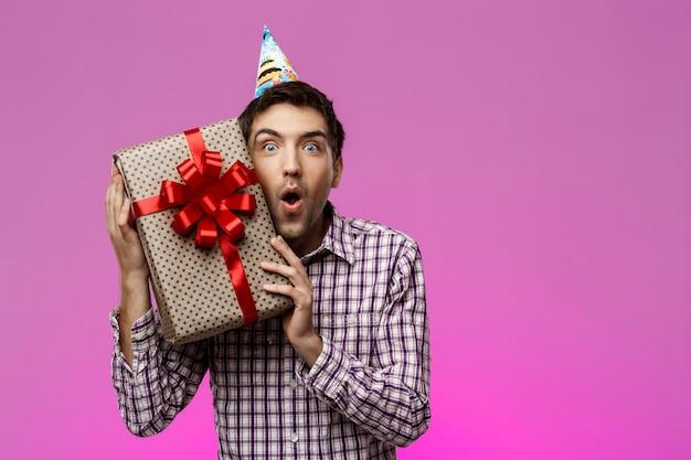 Glücklicher junger mann, der geburtstagsgeschenk im kasten über lila wand hält. Kostenlose Fotos