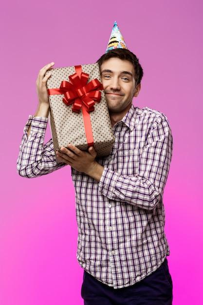 Glücklicher junger mann, der geburtstagsgeschenk im kasten über lila wand umarmt. Kostenlose Fotos