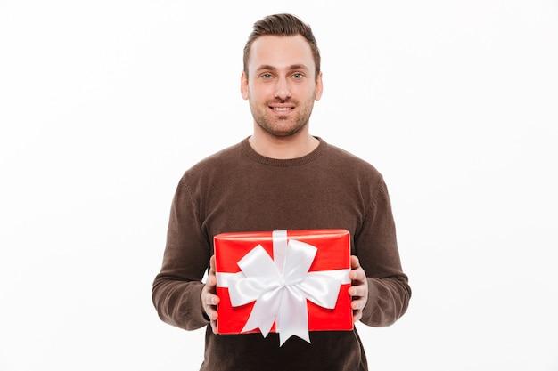Glücklicher junger mann, der geschenkboxüberraschung hält. Kostenlose Fotos