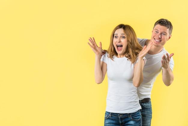 Glücklicher junger mann, der hinter der aufgeregten jungen frau schaut überrascht steht Kostenlose Fotos