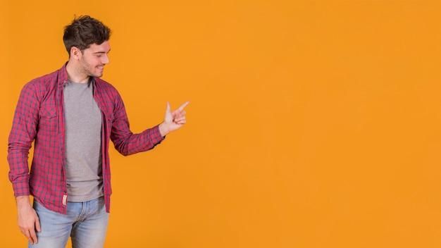 Glücklicher junger mann, der seinen finger gegen einen orange hintergrund zeigt Kostenlose Fotos