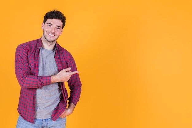 Glücklicher junger mann, der seinen finger gegen gelben hintergrund zeigt Kostenlose Fotos