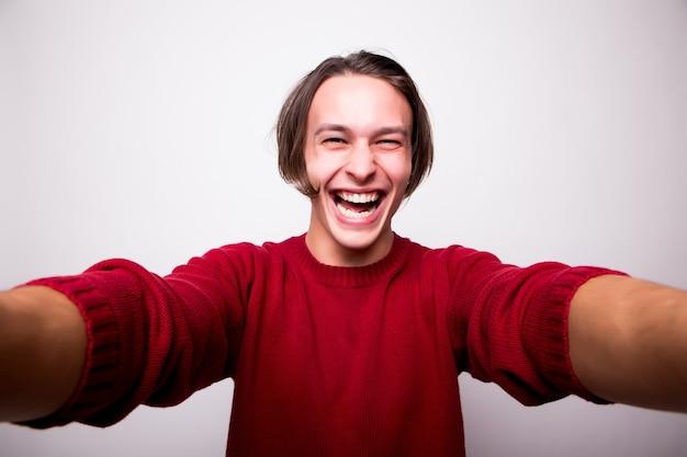 Glücklicher junger mann, der selbstporträtfotografie durch smartphone lokalisiert über weißer wand nimmt Kostenlose Fotos