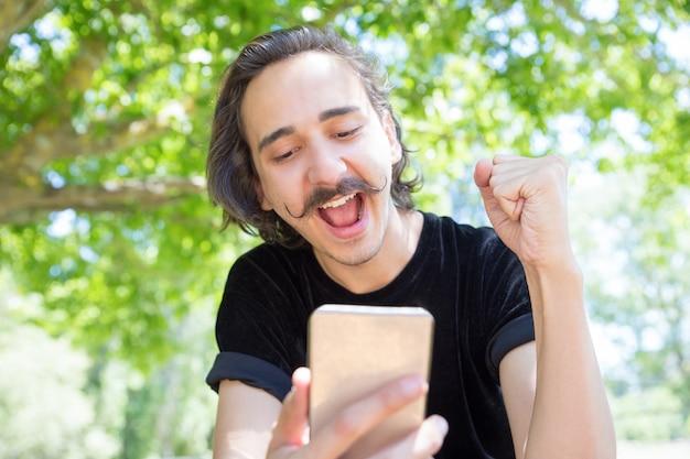 Glücklicher junger mann, der smartphone im park betrachtet. Kostenlose Fotos