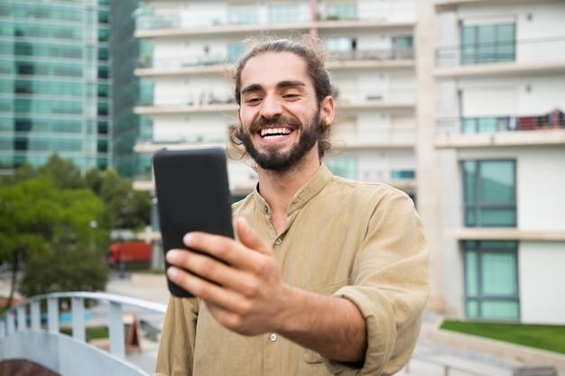 Glücklicher junger mann, der smartphone verwendet Kostenlose Fotos