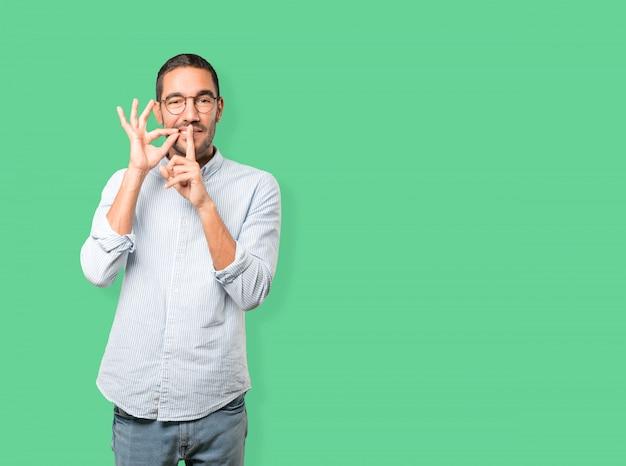 Glücklicher junger mann, der um die ruhe gestikuliert mit seinem finger bittet Premium Fotos