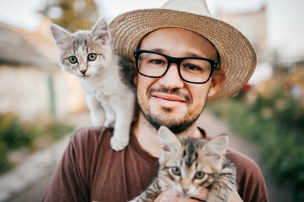 Glücklicher junger mann im strohhut, der das entzückende kätzchen zwei hält Premium Fotos