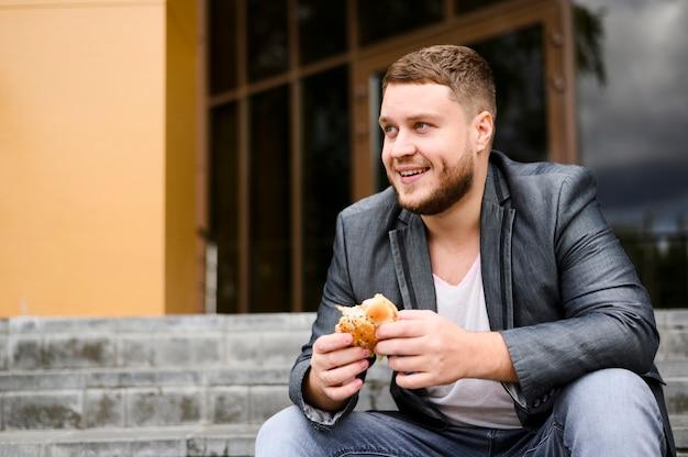 Glücklicher junger mann mit essen in seinen händen Kostenlose Fotos