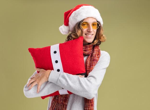 Glücklicher junger mann mit weihnachtsmütze und gelber