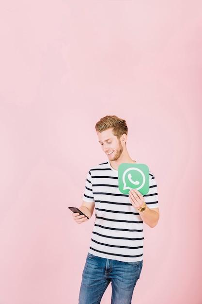 Glücklicher junger mann mit whatsapp ikone unter verwendung des smartphone Kostenlose Fotos