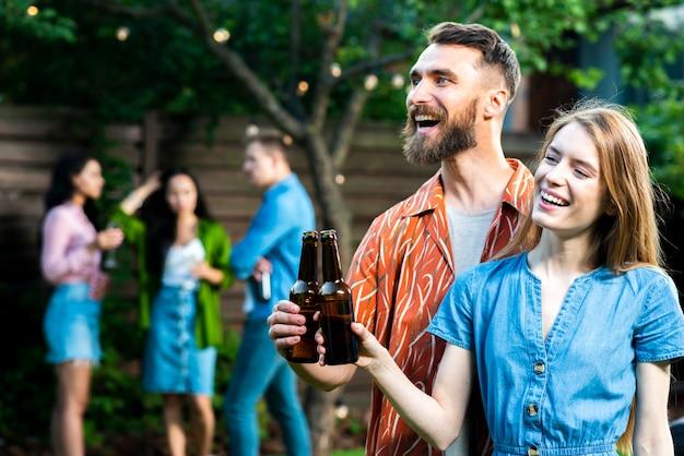 Glücklicher junger mann und frau, die bier röstet Kostenlose Fotos