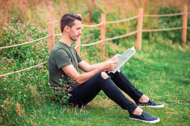 Glücklicher junger städtischer mann mit buch draußen Premium Fotos