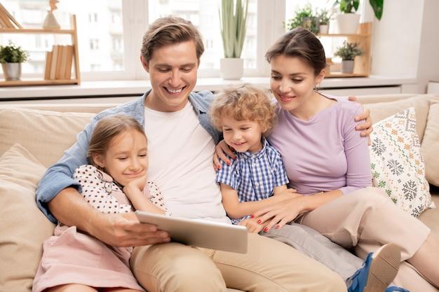 Glücklicher junger vater, der tablette hält, während seine frau und zwei niedliche kinder neben ihm sitzen Premium Fotos
