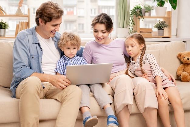 Glücklicher junger verheirateter mann und frau und zwei niedliche kinder, die laptopanzeige beim ansehen des films zu hause betrachten Premium Fotos