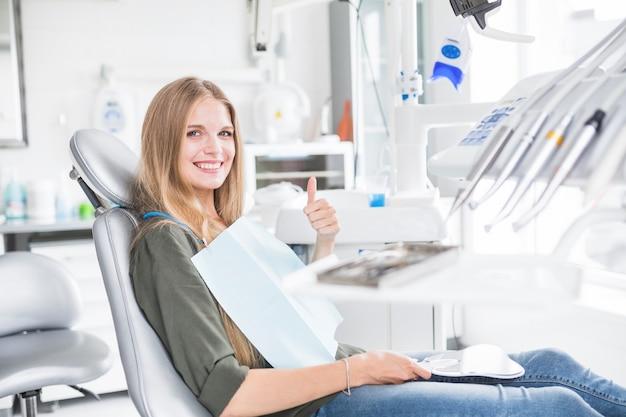 Glücklicher junger weiblicher patient, der auf dem zahnmedizinischen stuhl ok-zeichen gestikulierend sitzt Kostenlose Fotos
