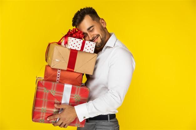 Glücklicher kerl, der kästen mit geschenken hält Kostenlose Fotos