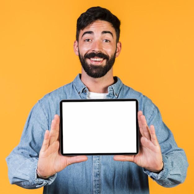 Glücklicher kerl der vorderansicht, der eine tablette hält Kostenlose Fotos