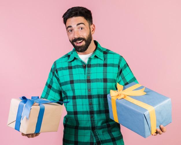 Glücklicher kerl des mittleren schusses, der geschenke hält Kostenlose Fotos