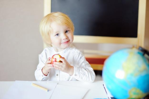 Glücklicher kleiner junge, der apfel am arbeitsplatz zeichnet und isst. Premium Fotos
