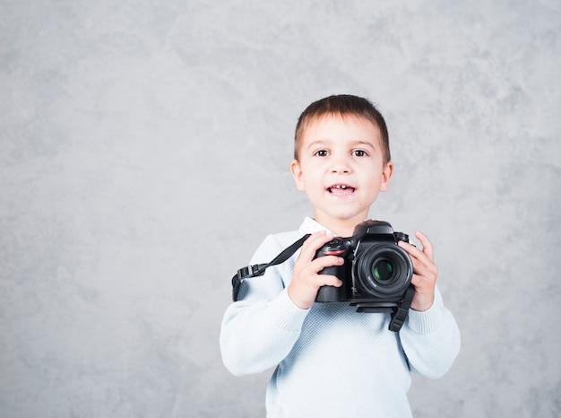Glücklicher kleiner junge, der mit kamera steht Kostenlose Fotos