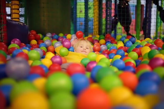 Glücklicher kleiner junge, der spaß in der ballgrube mit bunten bällen hat Premium Fotos