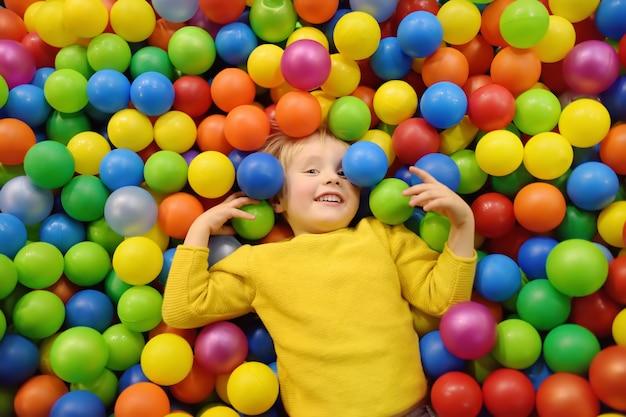 Glücklicher kleiner junge, der spaß in der ballgrube mit bunten bällen hat. Premium Fotos