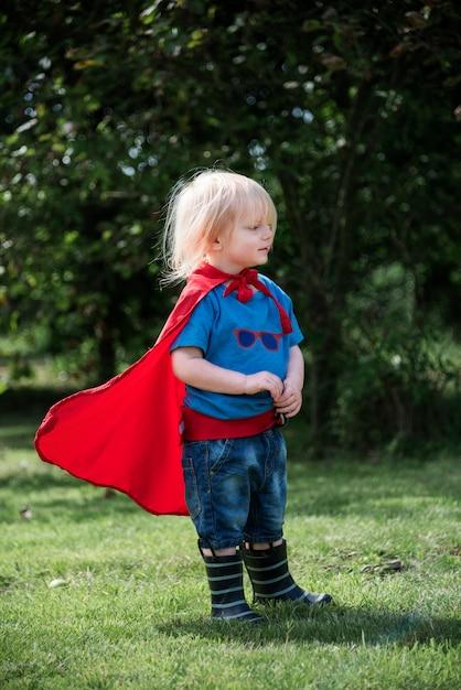 Glücklicher kleiner junge, der superhelden mit fantasie spielt Kostenlose Fotos