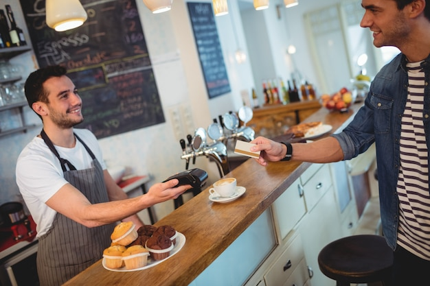 Glücklicher kunde und kellner an der kaffeestube Premium Fotos