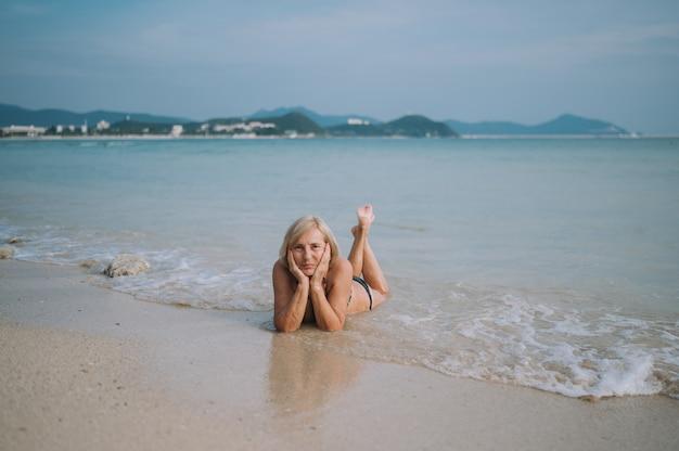 Glücklicher lächelnder aufgeregter älterer älterer frauentourist, der im wasser spielt und in den großen wellen auf dem ozeanseestrand schwimmt. reisen entlang asiens, aktives lifestyle-konzept. Premium Fotos