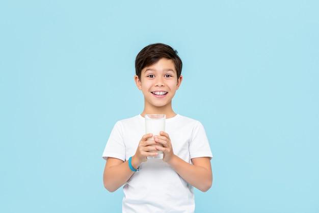 Glücklicher lächelnder gemischter rassenjunge, der frische milch trinkt, die auf hellblauer wand isoliert wird Premium Fotos