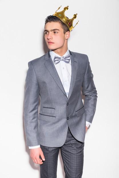 Glücklicher lächelnder geschäftsmann im grauen anzug und in der krone, lokalisiert über weißer wand Kostenlose Fotos