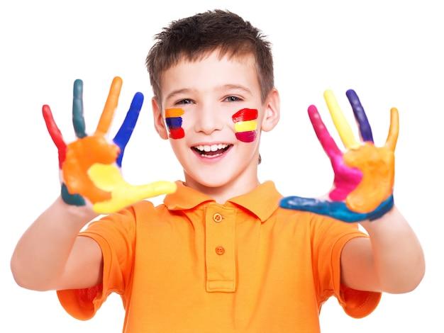 Glücklicher lächelnder junge mit gemalten händen und gesicht im orange t-shirt - auf einer weißen wand. Kostenlose Fotos