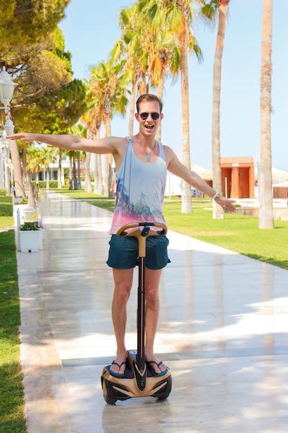 Glücklicher lächelnder junger mann auf segway. reitengyroscooter auf einer sonnigen sommerpalmengasse Premium Fotos