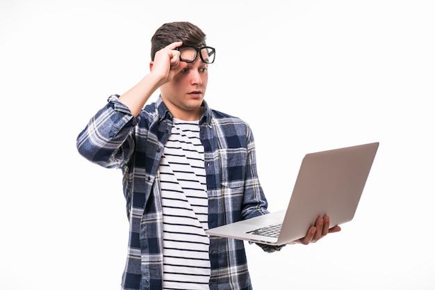 Glücklicher lächelnder junger mann, der computer beobachtet und arbeitet Kostenlose Fotos