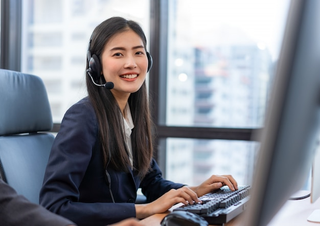 Glücklicher lächelnder kundendienstmitarbeiter der asiatischen frau des betreibers mit kopfhörern Premium Fotos
