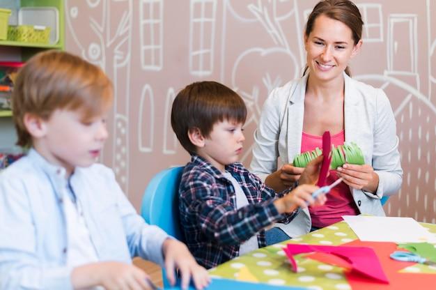 Glücklicher lehrer, der papier mit kindern schneidet Kostenlose Fotos