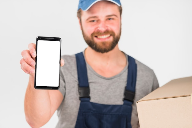 Glücklicher lieferer, der kasten und smartphone mit leerem bildschirm hält Kostenlose Fotos