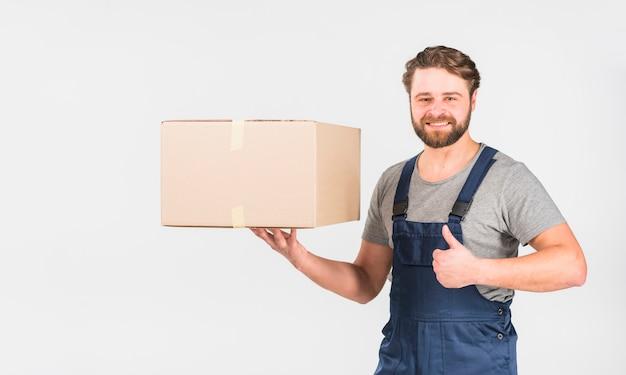 Glücklicher lieferer mit dem kasten, der sich daumen zeigt Kostenlose Fotos