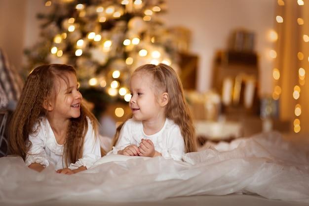 Glücklicher mädchenschwesterhintergrund von goldenen bokeh weihnachtslichtern Premium Fotos