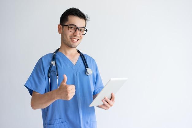 Glücklicher männlicher doktor, der tablette hält und sich daumen zeigt Kostenlose Fotos