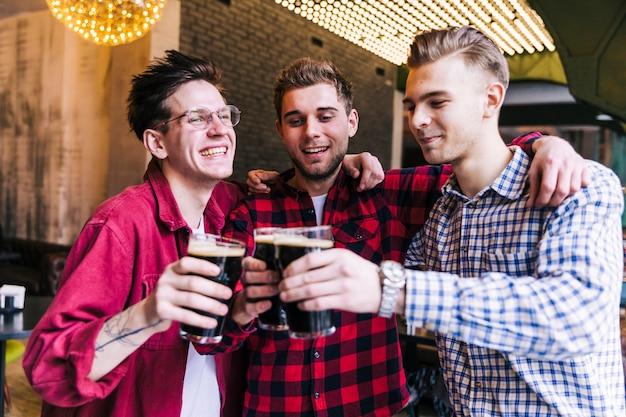 Glücklicher männlicher freund, der beifall mit biergläsern macht Kostenlose Fotos