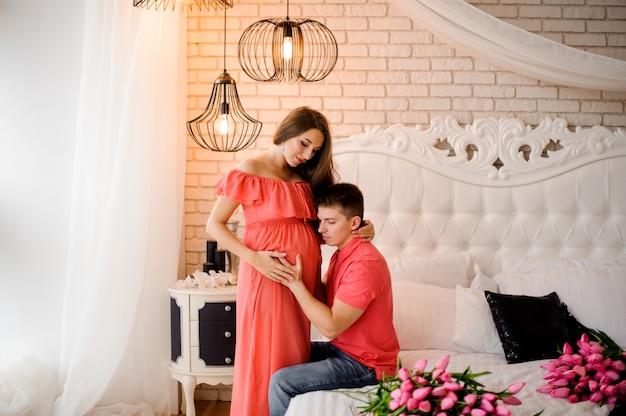 Glücklicher mann, der auf den bauch seiner schönen schwangeren frau hört Premium Fotos